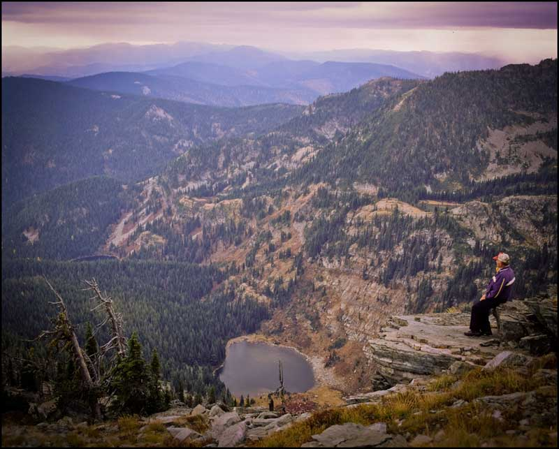 Wide perspective of Jim Cyr sitting on a ledge at the top of Eagle Peak looking out over Hub Lake and the vast Western Montana Wilderness of Mineral County.